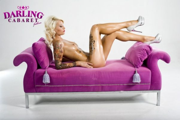 Amazing stripper shows her sexy legs on sofa on the stage of the best strip club in Prague