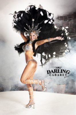 Brazilian striptease show in Prague by naked girl southerner with big ass and tits on stage at Darling Cabaret. Striptease girl has hat with cabaret show plumes.