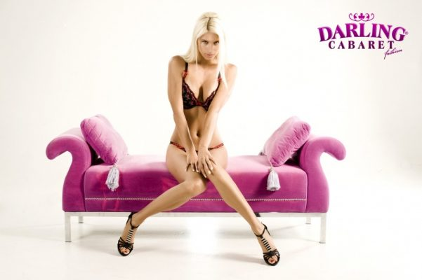 Beautiful stripper sitting on the pink on pink sofa at the best strip club in Prague