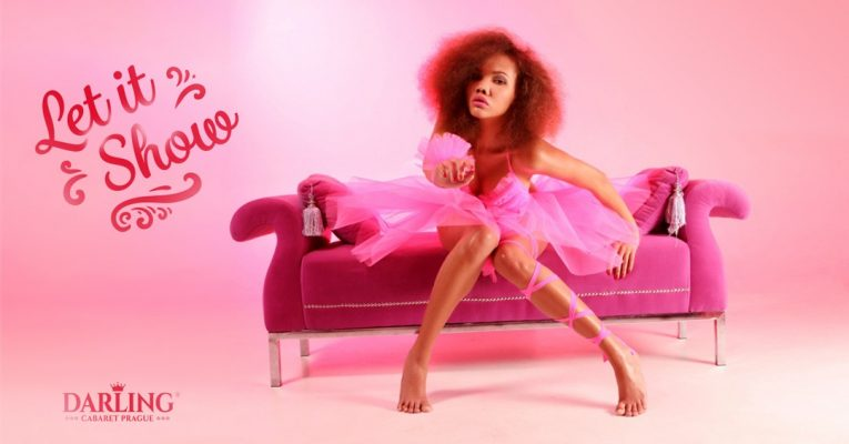 Sexy black girl in Prague with pink dress is at photo shooting on a sofa at Darling cabaret in Prague.