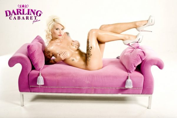 Beautiful stripper sitting on the pink and hiding her nipples on sofa at the best strip club in Prague